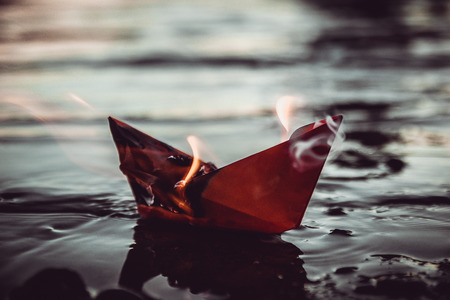 A paper ship burns on fire