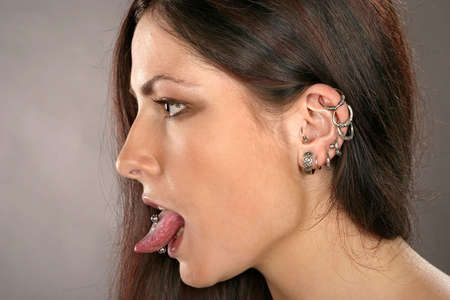 girl tongue: auburn-haired girl, woman with ear-rings and studs Stock Photo