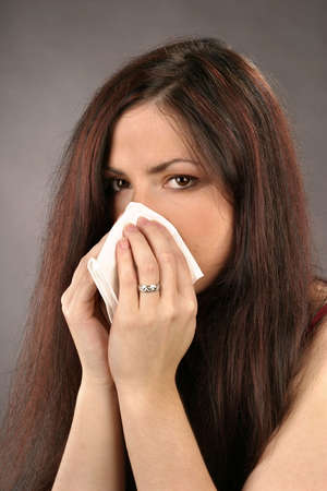 auburn haired girl, young woman wiping her nose Stock Photo