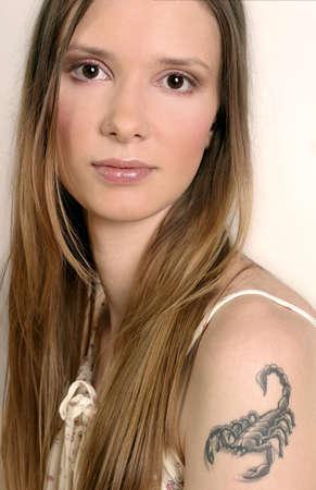 escorpio: mujer joven, muchacha con un tatoo del escorpi�n en su brazo Foto de archivo
