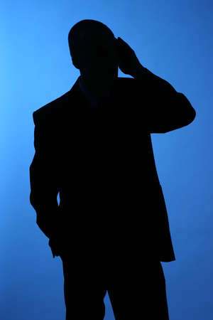 elegant man, businesman in  a suit talking on a phone-sillhuette photo
