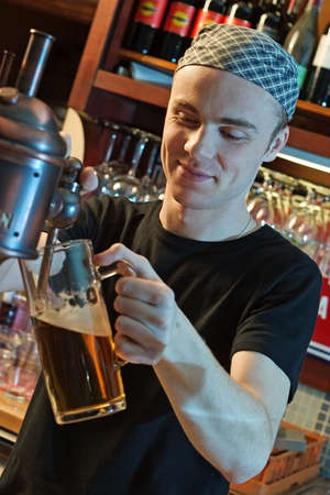 young man at a bar counter pouring beer