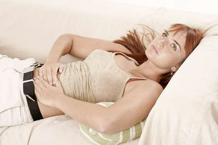 indigestion: red-haired young girl, woman on a sofa