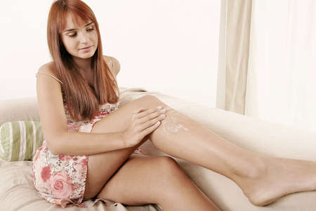 womanhood: red-haired young girl, woman putting some cream  Stock Photo