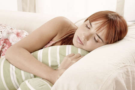 red-haired young girl, woman sleeping on a sofa photo