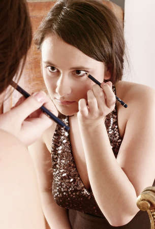 womanhood: auburn-haired girl, young woman putting make up in front of  a mirror