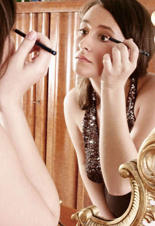 auburn-haired girl, young woman putting make up in front of  a mirror