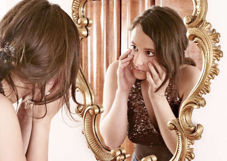 auburn-haired girl, young woman  in front of  a mirror Stock Photo