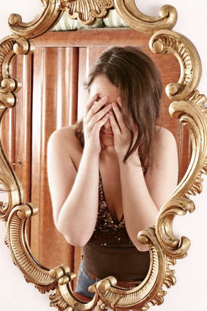 womanhood: auburn-haired girl, young woman  in front of  a mirror Stock Photo