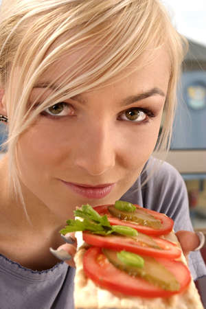 blond, young girl, woman eating a tomato sandwich