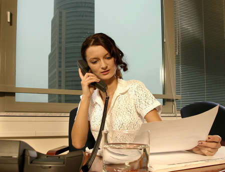 girl, young woman talking on a phone in an office photo