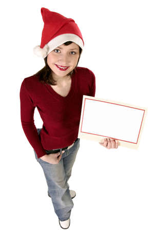 Young woman wearing Santa hat holding a card, add text here Stock Photo - 586472
