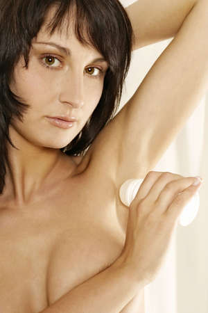 young girl, woman using a roll-on deodorant-on white photo