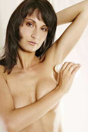armpits: young girl, woman using a roll-on deodorant-on white