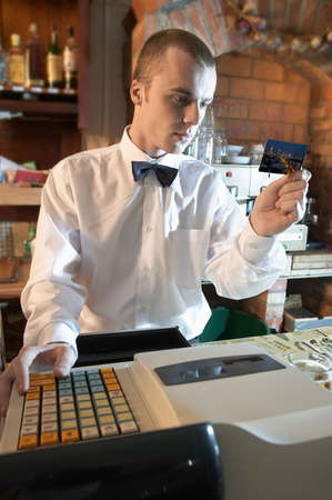young weiter, barman verifying credit card or cheating