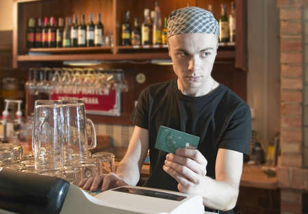 trickery: young  barman verifying credit card or cheating