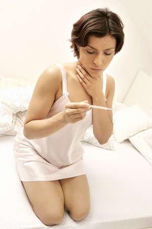 Jeune femme, fille d'une nuit-dresst malades contrôle de température  Banque d'images - 595668
