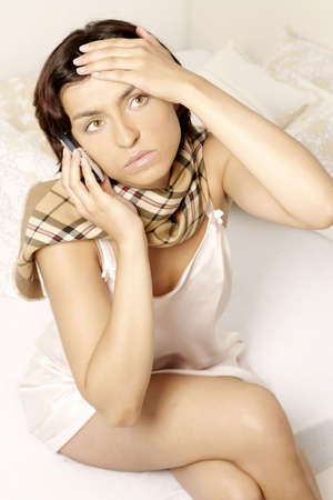 phonecall: young woman, girl with a sore throat and headache making a phonecall