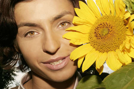 portrait of a young woman, brunette with a sunflower-close up  photo