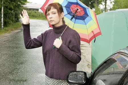 portrait of a young woman with an umbrella, standing by a broken car Banco de Imagens