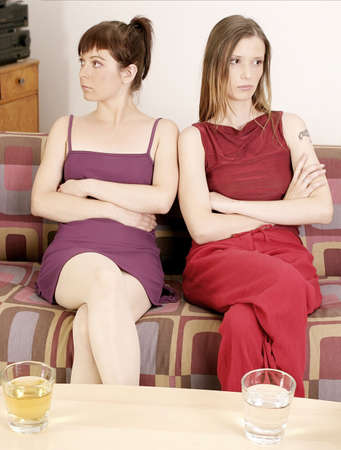 opposite: two girls young women sitting on a sofa, looking opposite direction Stock Photo