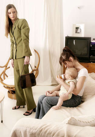 babysitter: working mother leaving a baby at home with a babysitter Stock Photo