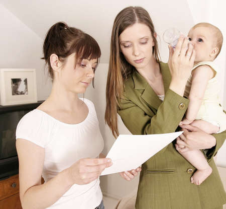 working mother leaving a baby at home with a babysitter Stock Photo