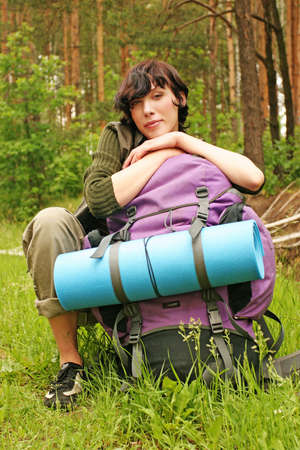 girl, young woman with a backpack hiking in a  forest-resting