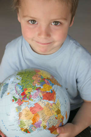 child, small boy holding a colourfull ball-a globe