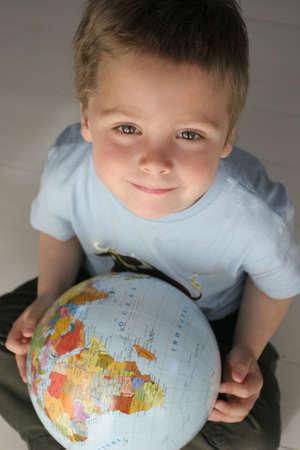 descubridor: ni�o, muchacho peque�o que sostiene un globo de la bola-uno del colourfull Foto de archivo