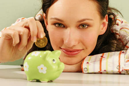 saving money-young woman putting a coin into a green money-box-close up photo