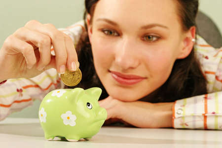 contentment: saving money-young woman putting a coin into a green money-box-close up Stock Photo