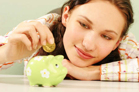 saving money-young woman putting a coin into a green money-box-close up Stock Photo