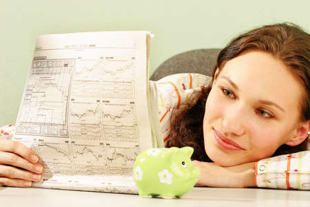woman reading business statistics of a stock market -with a piggy bank on a desk