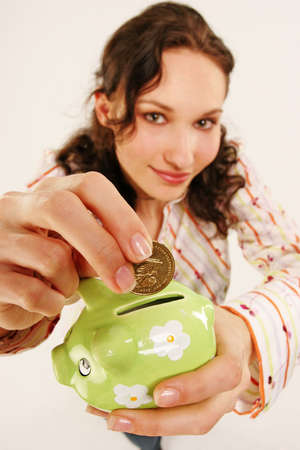 saving money-young woman putting a coin into a green money-box Stock Photo