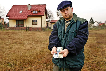 Farmer shoving polish currency notes - house in a background  Stock Photo