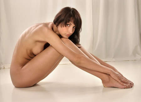naked woman, brunette sitting with white background Stock Photo
