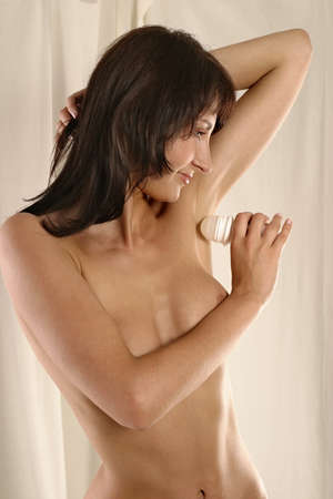young woman  pampering-using a deodorant photo