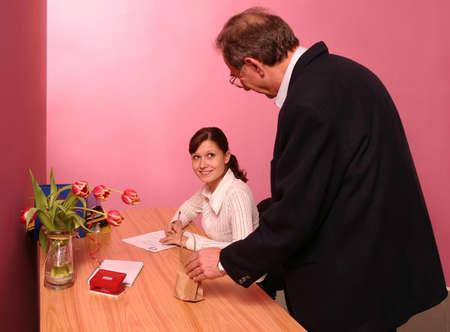 ambiente laboral: trabaje a hombre del ambiente que trae un poco de regalo para una mujer que trabaja en oficina