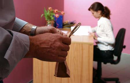 ambiente laboral: entorno de trabajo-hombre con lo que algunos regalo para una mujer que trabaja en un segundo plano  Foto de archivo