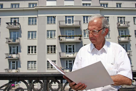 appartment: architect studying plans of house in front of appartment block  Stock Photo