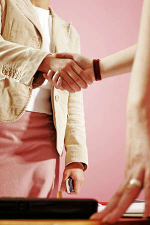 two young woman shake hands in work environment   photo
