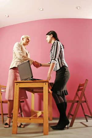 ambiente laboral: dos manos de la sacudida de la mujer de los j�venes en el ambiente del trabajo Foto de archivo