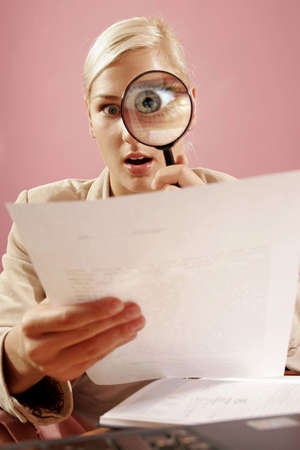 supervise:  work environment- woman with a magnifying glass over some paperwork in modern office-on pink