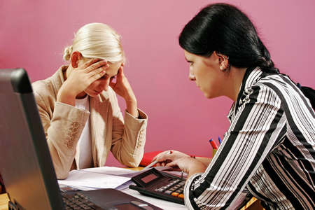 two young women discuss over some paperwork-on pink   Stock Photo