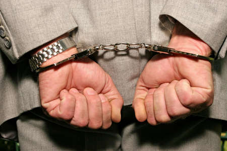 Arrested man in a business suit - hands in cuffs - close up    photo