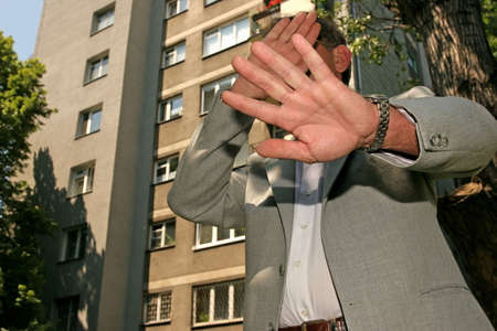man in a business suit hiding his face from the photographer Stock Photo