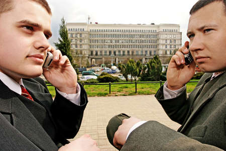 disscuss: two man on a street talking on their mobiles- buildings in the background