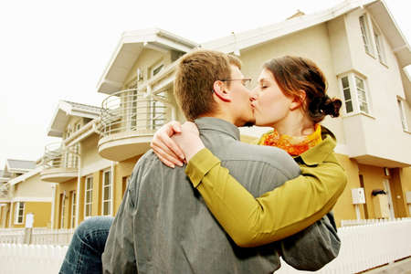couple in front of one-family house in modern residential area  Stock Photo