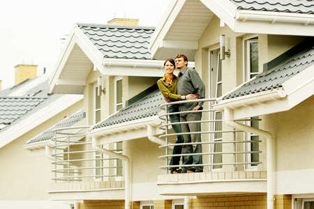 appartment: couple in front of one-family house in modern residential area  Stock Photo